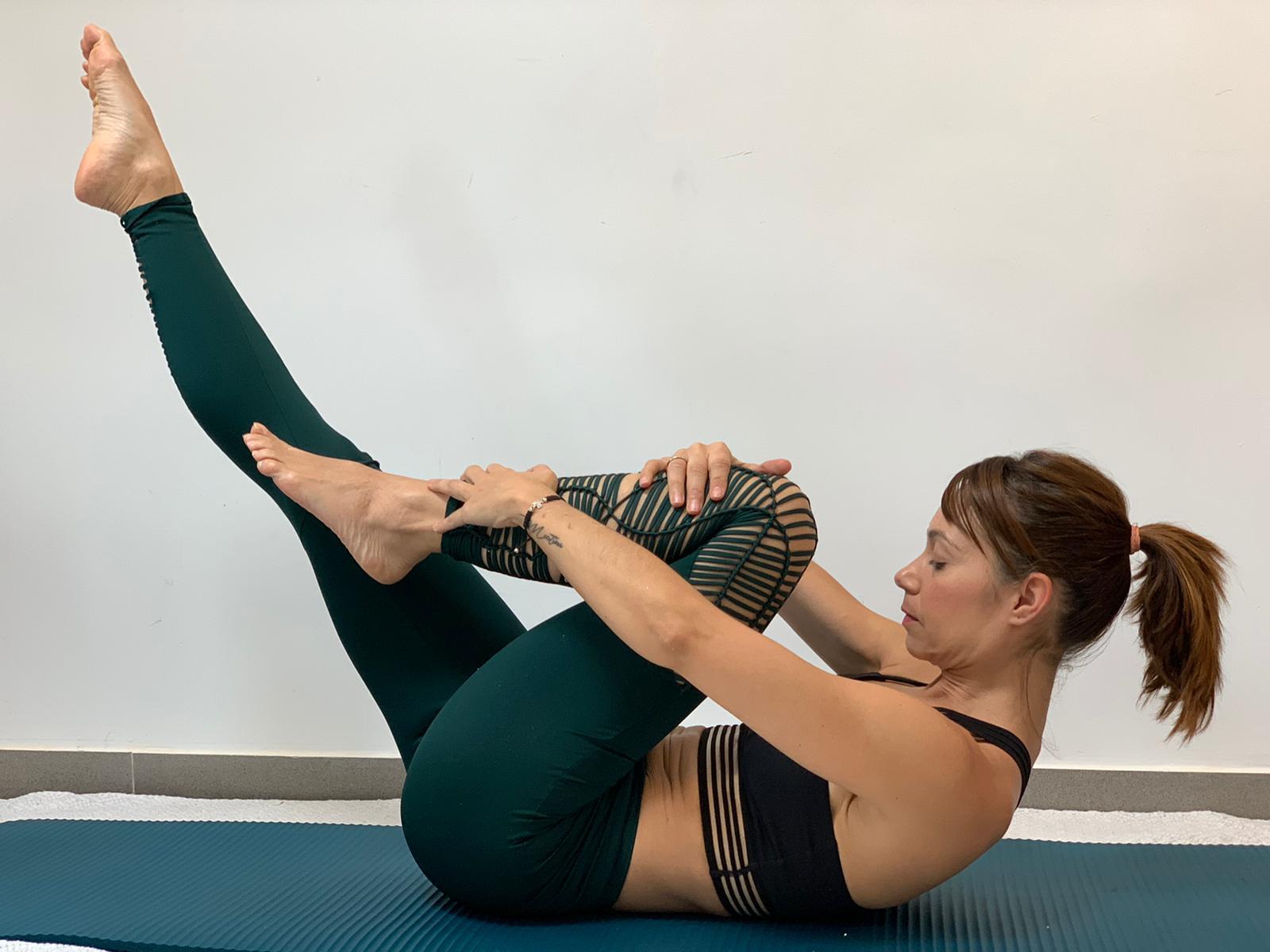Clases de Pilates en la colchoneta en Madrid. Nuestra profesora Noelia realizando el ejercicio Single Leg Stretch.